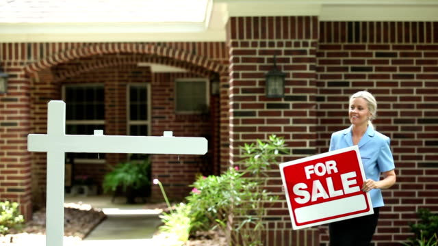 "real estate agent places ""for sale"" sign. home. - selling stock videos and b-roll footage"