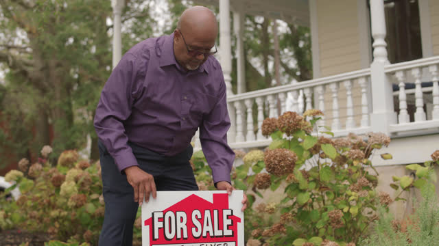 "real estate agent plants a ""for sale"" sign in the front yard - landscaped stock videos & royalty-free footage"