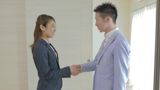 real estate agent shaking hands and handing keys over to buyer - 住宅購入点の映像素材/bロール