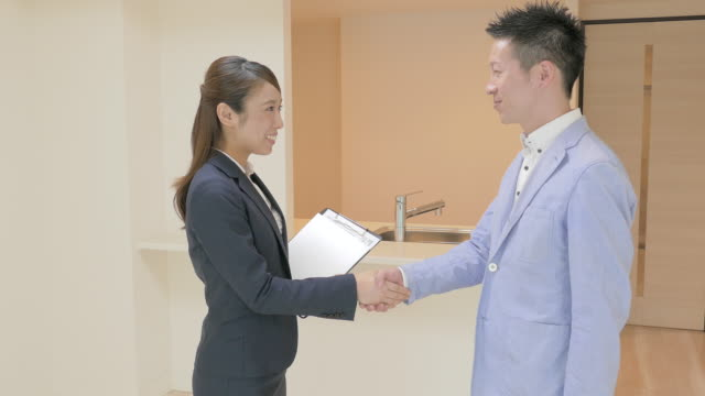 real estate agent shaking hands with buyer - 住宅購入点の映像素材/bロール