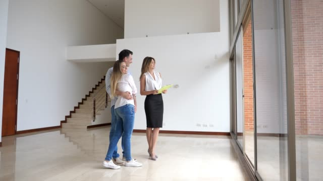 real estate agent showing a young couple a modern apartment both looking very happy - estate agent stock videos & royalty-free footage