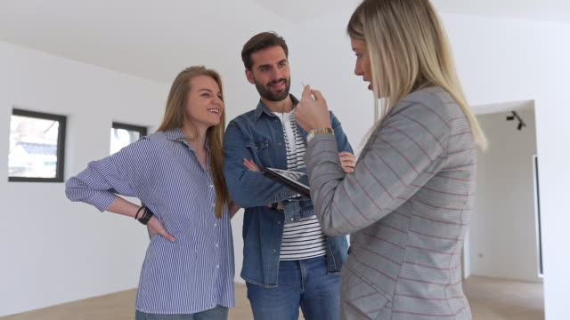 real estate agent showing a young couple a new house - real estate stock videos & royalty-free footage