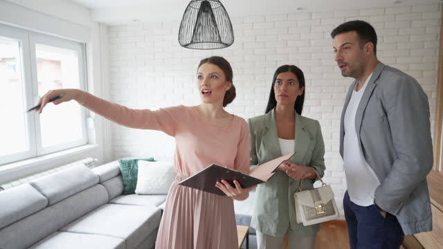 real estate agent showing apartment for sale to a young couple - real estate stock videos & royalty-free footage