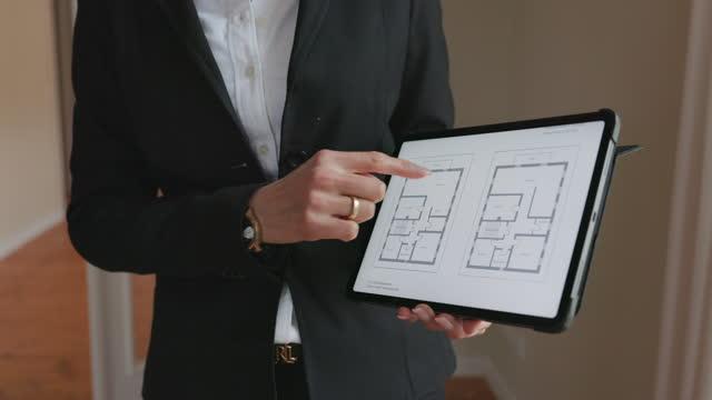 agente immobiliare che mostra la planimetria - architetto video stock e b–roll