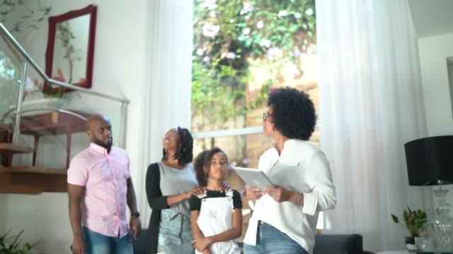 real estate agent showing house to a family - strategia di vendita video stock e b–roll