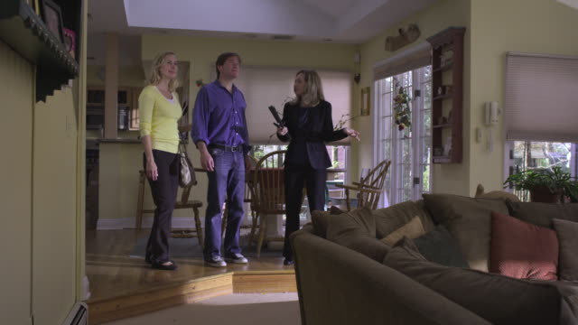 vidéos et rushes de ws ds real estate agent showing interior of home to couple / wyckoff, new jersey, usa - homme dans un groupe de femmes