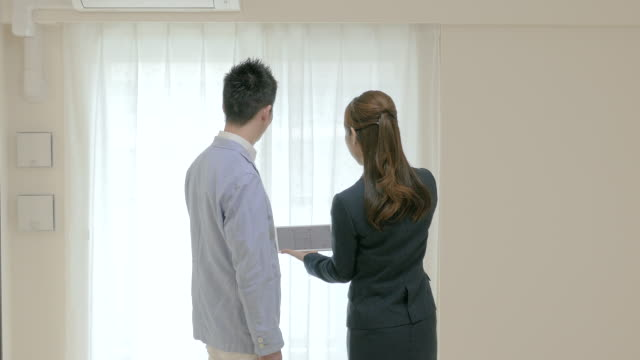 Real Estate Agent Showing Rooms to Buyers on Tablet