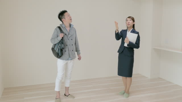 real estate agent showing rooms to buyers - 買う点の映像素材/bロール