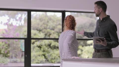 vidéos et rushes de real estate agent showing young adult woman house - vendeur
