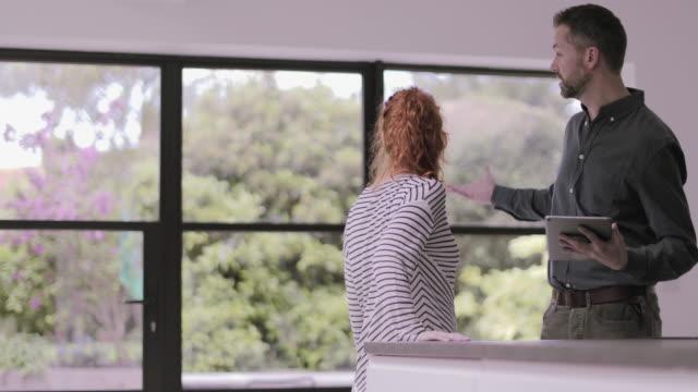 vidéos et rushes de real estate agent showing young adult woman house - immobilier