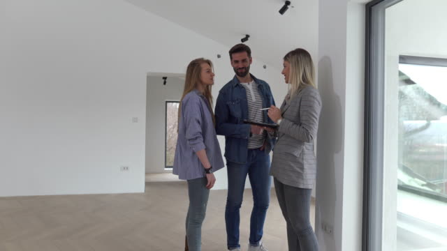 real estate agent shows bright new apartment to a young couple - searching video stock e b–roll
