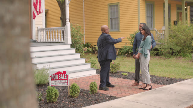 a real estate agent shows off the neighborhood to a married couple - zweistöckiges wohnhaus stock-videos und b-roll-filmmaterial