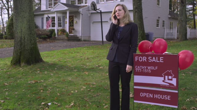 ms tu real estate agent standing next to for sale sign posted on  lawn of house, talking on phone / wyckoff, new jersey, usa - estate agent sign stock videos & royalty-free footage