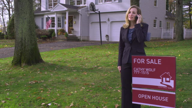 ms tu real estate agent standing next to for sale sign posted on the lawn of house, talking on phone / wyckoff, new jersey, usa - estate agent sign stock videos & royalty-free footage