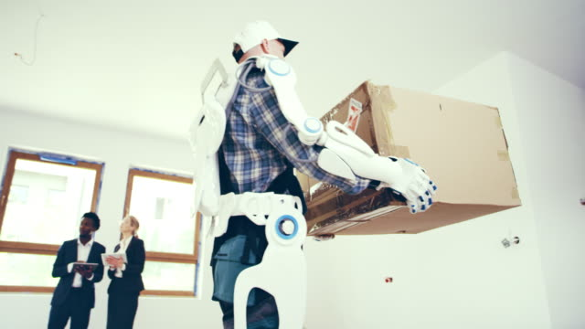 vídeos de stock e filmes b-roll de real estate agents furnishing apartment. worker in exoskeleton carrying boxes - design plano