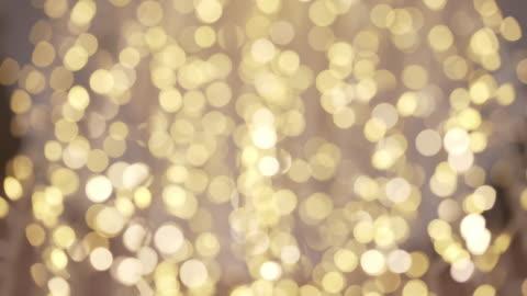 echte goldene dekoration licht in defokussierten gold glitter hintergrund abstrakte bewegen - fairy lights stock-videos und b-roll-filmmaterial