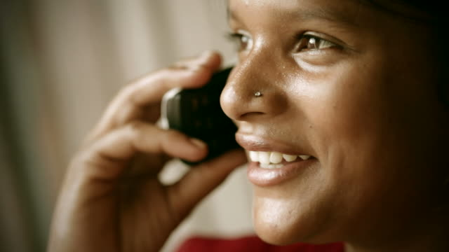 real people from india: young woman happily talking on phone. - nose piercing stock videos & royalty-free footage