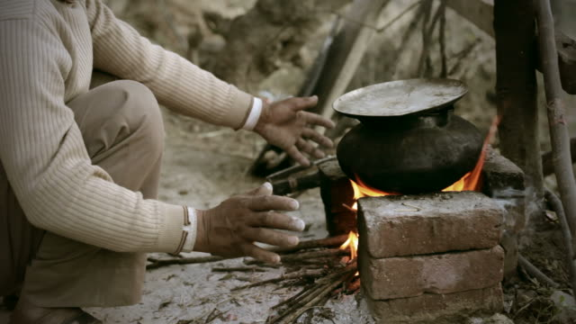 vídeos de stock, filmes e b-roll de pessoas reais da índia rural: homem cozinhar alimentos na fogueira - firewood
