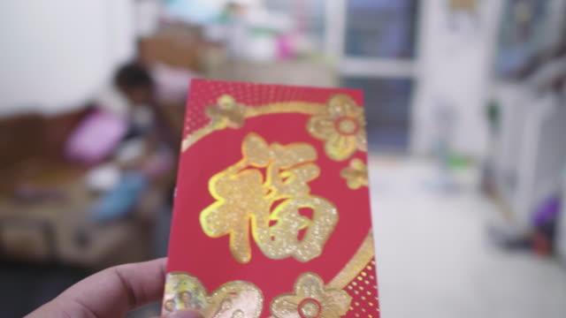stockvideo's en b-roll-footage met echte mensen krijgen rode pakketten in nieuwe jaar. - chinees nieuwjaar