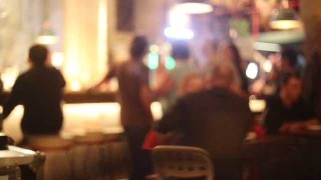 vídeos de stock e filmes b-roll de pessoas reais ter bom tempo no bar à noite. - movimento desfocado