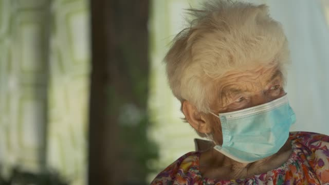 real people senior woman wearing mask to avoid infectious diseases. looking at camera and smiling - obscured face stock videos & royalty-free footage