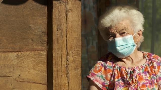 vidéos et rushes de personnes réelles femme âgée portant le masque pour éviter les maladies infectieuses. regarder la caméra et le sourire - retraite