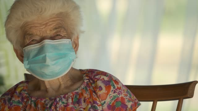 real people senior woman wearing mask to avoid infectious diseases. looking at camera and smiling - over 80 stock videos & royalty-free footage