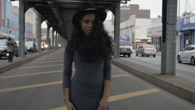 vídeos de stock, filmes e b-roll de real person black woman poses for the camera at a brooklyn, nyc subway station - 4k - passagem subterrânea via pública