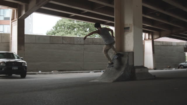 A real person skateboards underneath a New York City highway