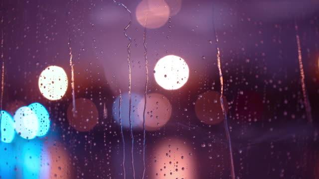 4k echte regentropfen auf einem auto oder hausfenster mit verschwommenen hintergrund der nacht stadt lichter gefühl lonliness - hergestellter gegenstand stock-videos und b-roll-filmmaterial