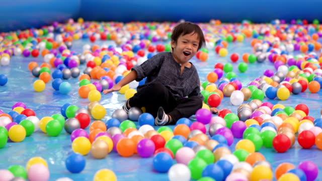 vídeos y material grabado en eventos de stock de en tiempo real 4k niño cayendo mientras corre en pelotas parque infantil piscina - planta del pie
