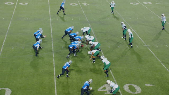 vidéos et rushes de ws real time. aerial view. professional football teams break huddle and come to line of scrimmage, quarterback throws an interception and receiving player runs ball out of bounds and celebrates turnover with teammates. - football américain