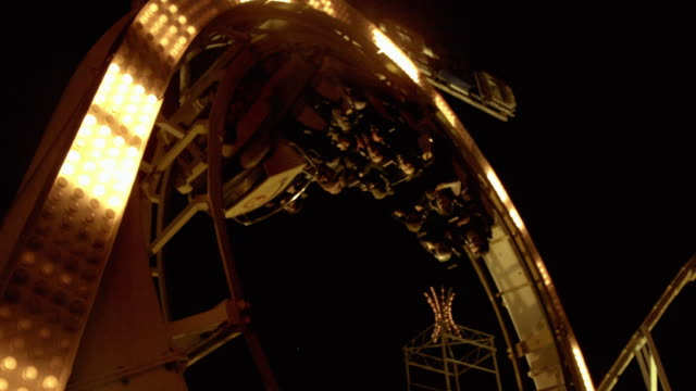 real time and slow motion shots of a roller coaster doing a loop the loop at night time - fairground stock videos and b-roll footage