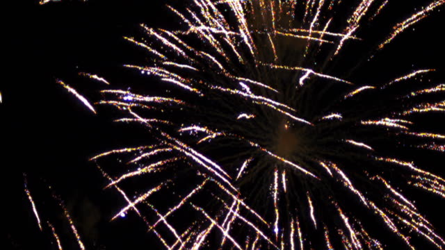 Real time and slow motion shots of fire works exploding in the night sky