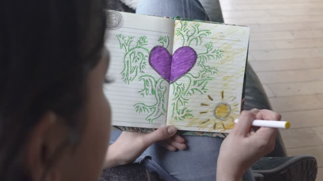 real time clip of a young woman colouring in a heart - diary stock videos & royalty-free footage