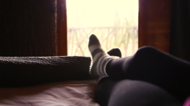 vídeos de stock, filmes e b-roll de real time footage of girl laying on bed from personal perspective playing with feet wearing hairy socks from a nice tree house during travel vacations. - treehouse
