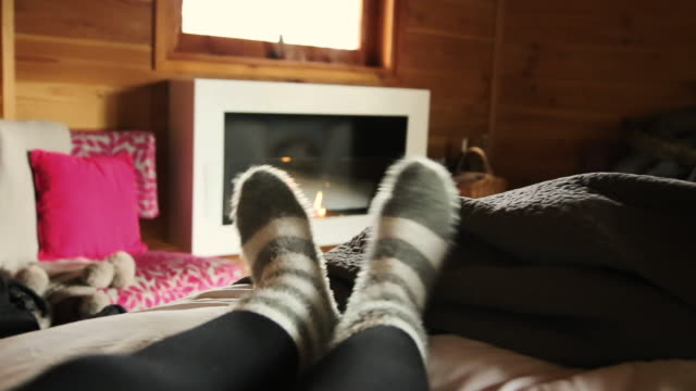 Real time footage of girl laying on bed from personal perspective playing with feet wearing hairy socks and nice fireplace in a tree house during travel vacations.