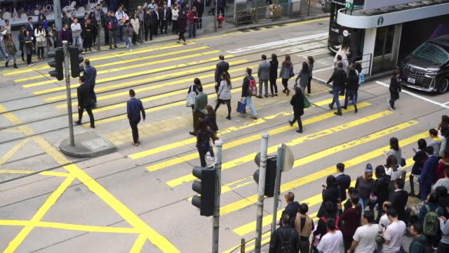 echtzeit: menschen, die die straße am zebrastreifen in hong kong überqueren. - central bezirk hongkong stock-videos und b-roll-filmmaterial