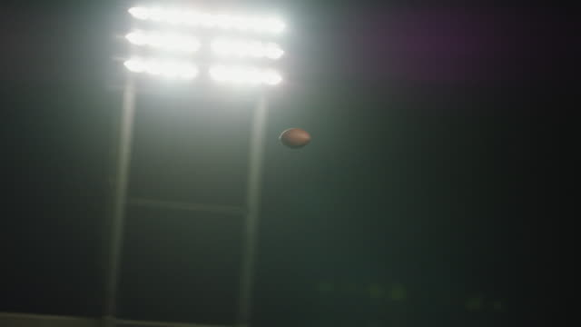 Real Time. Spiraling football soars over playing field under bright stadium lights.