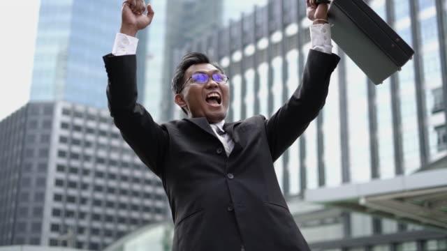 vídeos de stock e filmes b-roll de real time: successful businessman, he are arms raised and smiling. - camisa e gravata