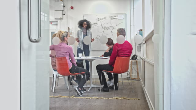 Real time video of a multi-ethnic creative business people brainstorming in conference room
