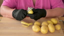 Real time video of a womans hands in black gloves to peeling potatoes to make fries in a domestic kitchen