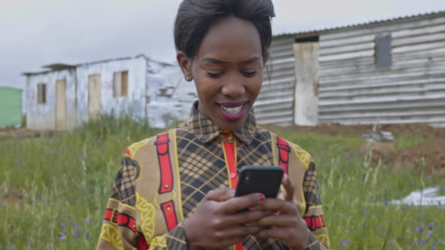 real time video of a young black woman using mobile phone outdoors. - township stock videos & royalty-free footage