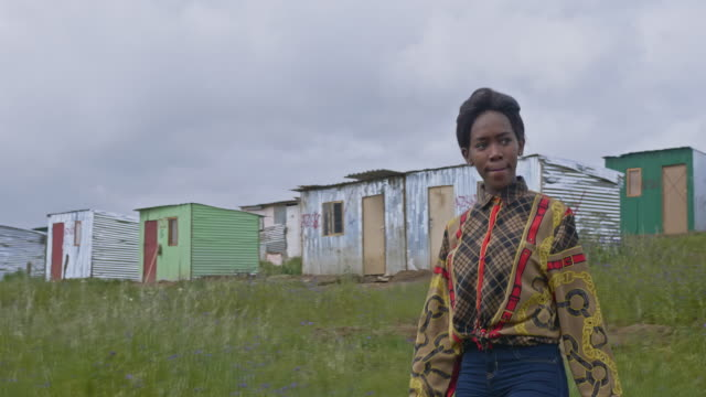 real time video of a young black woman walking in a township, south africa - poverty stock videos & royalty-free footage