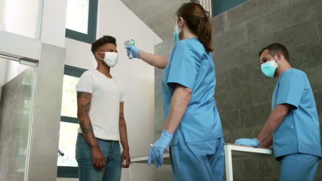 vídeos y material grabado en eventos de stock de video en tiempo real del hombre afrocaribeño que tiene un control de pandemia en la entrada del hospital - trabajador de primera línea
