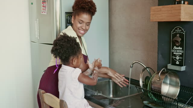real time video of afro-caribbean mother and daughter washing hands at kitchen - sticky stock videos & royalty-free footage