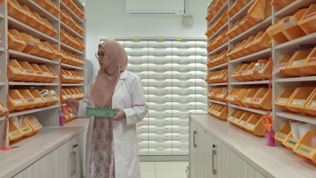 real time video of asian muslim pharmacist working at pharmacy - compartment stock videos & royalty-free footage