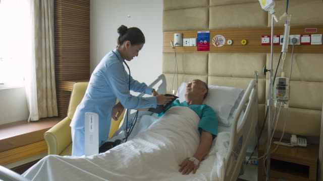 vídeos de stock e filmes b-roll de real time video of asian nurse checking senior man's blood pressure at hospital - profissional de enfermagem