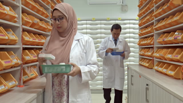 real time video of asian pharmacists choosing medication at pharmacy - religious dress stock videos & royalty-free footage