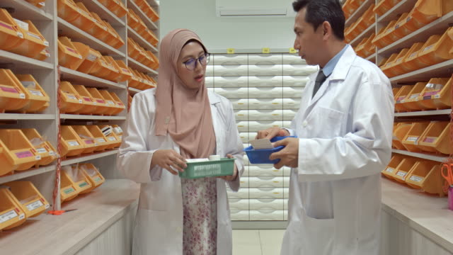 real time video of asian pharmacists talking about the medication at pharmacy - prescription medicine stock videos & royalty-free footage